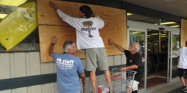 Employees help board up the Piggly Wiggly grocery store as it closes on in South Carolina. Photo / AP