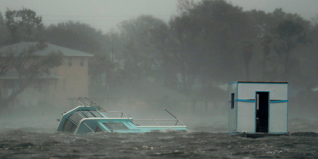 A boat is partially submerged in the Halifax River as Hurricane Matthew moves through Daytona Beach. Photo: AP/Charlie Riedel