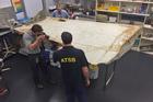 Australian Transport Safety Bureau staff examine a piece of MH370 debris at their laboratory in Canberra, Australia. Photo / AP