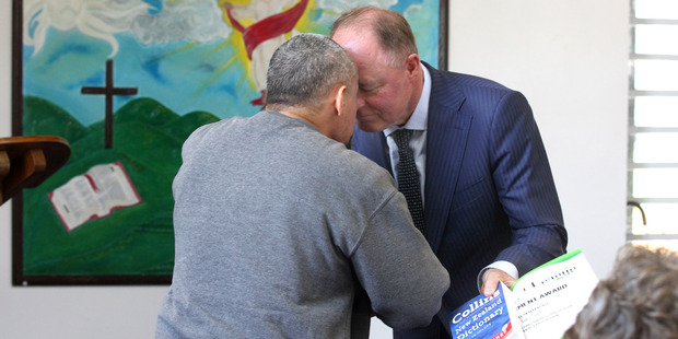 A prisoner accepts his certificate and a dictionary, presented by Craig Foss, National MP, Tukituki, after graduating.