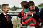 Co-trainers Lance O'Sullivan (left) and Andrew Scott, hugging jockey Craig Grylls. Photo / Warren Buckland