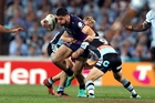 Jesse Bromwich attempts to shrug off tacklers in the grand final. The loss to the Sharks was shattering, he says. Photo / photosport.nz