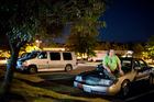 John Baird Jr. smokes on the hood of his 2004 Mercury Grand Marquis sedan.  Photo / The Washington Post / Sarah L. Voisin