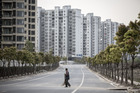 A worker holding a broom crosses a road in front of residential buildings in the Jiading district of Shanghai. Photo / Bloomberg