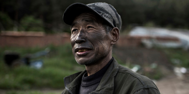 A worker from a graphite factory, his face covered with the mineral, makes his way home in Mashan, in the far northeastern province of Heilongjiang. Photo / Michael Robinson Chavez