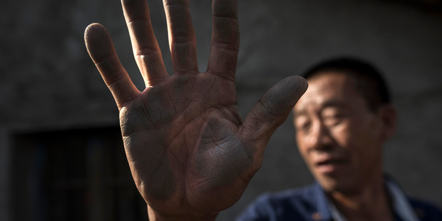 Lyu Shengwen, 55, shows the graphite dust he collected on the side of his house, which he cleaned the day before, in the town of Mashan, China. Photo / Washington Post, Michael Robinson Chavez