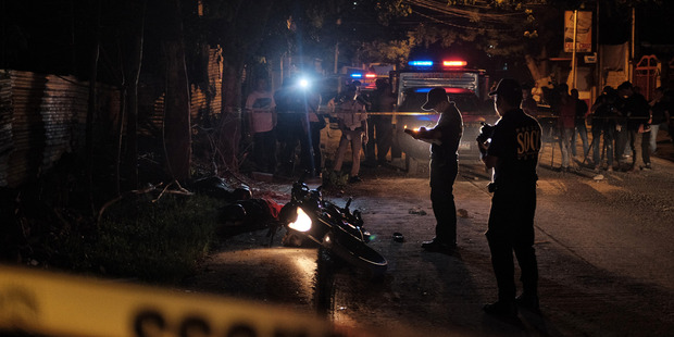 Investigators examine the bodies of two suspected drug dealers who were fatally shot by police in a suburban area of Pasig city last month. Photo / The Washington Post