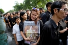 Thousands of Thai citizens lined up outside the Grand Palace in Bangkok, many holding portraits of the King, to offer their condolences. Picture / AP