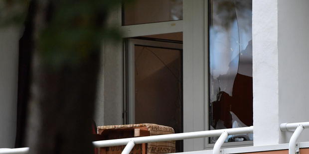 A shattered window pane is pictured in a residential property in the Yorck area of Chemnitz, eastern Germany, where police raided a property. Photo / AP