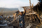 A child carries a container of water as he walks past homes destroyed by Hurricane Matthew in Jeremie, Haiti. Photo / AP