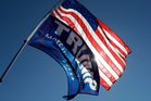 A supporter of Republican Donald Trump holds the American flag and a Trump flag outside a campaign stop by Democratic presidential candidate Hillary Clinton in Detroit. Photo / AP