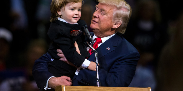 Republican Presidential nominee Donald Trump holds 2-year-old Hunter Tirpak of Tuscarora, Pennsylvania, who is dressed as Trump, during a rally. Photo / AP