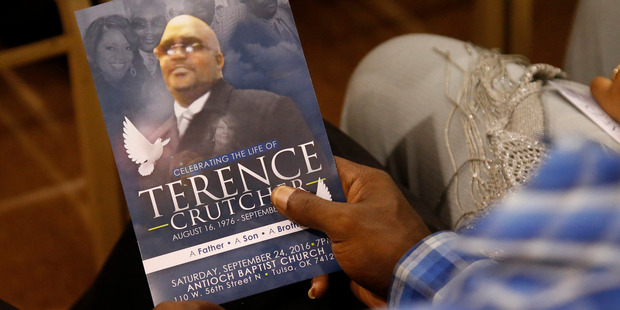 A man holds a copy of the programme for the funeral in September of Terence Crutcher. Photo / AP