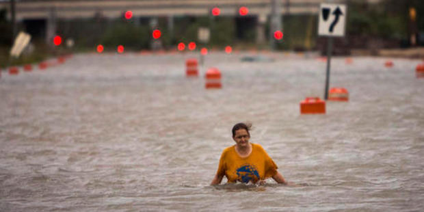 A woman who identified herself as Valerie walks along flooded President Street after leaving her homeless camp after Hurricane Matthew caused flooding. Photo / AP