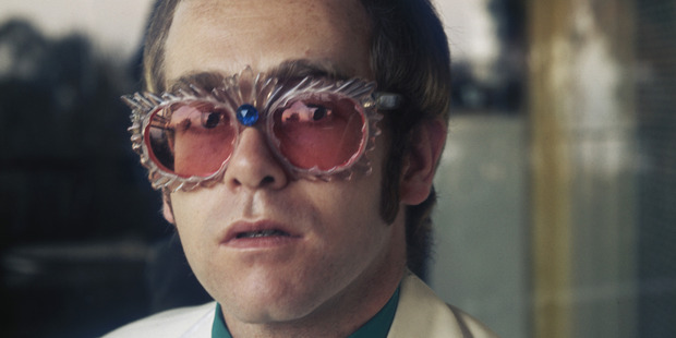 English pop singer Elton John in a white jacket and rococco spectacles during a photoshoot at his home for his 1974 Greatest Hits album, 1974. Photo / Getty
