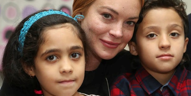 Hollywood actress Lindsay Lohan poses with a Syrian refugee family at their house after the visit to a hospital built for Syrian refugees at Sultanbeyli. Photo / Getty