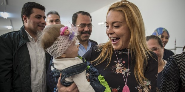 American actress Lindsay Lohan holds a baby in her arms during her visit at a container town where Syrian refugees live in the Nizip district of Gaziantep in Turkey. Photo / Getty