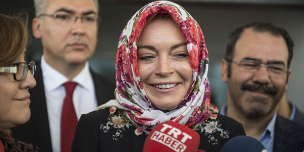 American actress Lindsay Lohan speaks to press members with wearing a headscarf given by a Syrian woman, after her visit at a container town where Syrian refugees live. Photo / Getty
