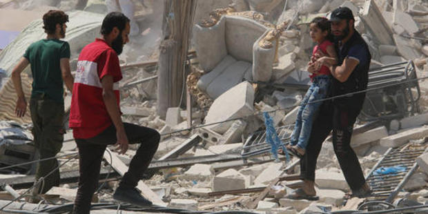 A Syrian man carrys a girl away from the rubble of a destroyed building. Photo / AMC