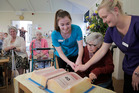 Masonic Court's oldest resident Trixie Seccombe, 100, cuts the cake with the youngest staff members Brylee Kemp (left) and Kylie Pointon (right), both 21. PHOTO/BEVAN CONLEY