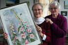 Wanganui Arts Society members Barbara Vine, right, and Janette Cutten with Ms Cutten's watercolour portrait of foxgloves. PHOTO/STUART MUNRO