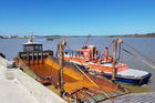 The pilot boat manouevres the dredge into place. PHOTO/PORT WHANGANUI