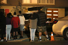 Family members gather outside a house in School Road Te Atatu as the body of a stabbing victim is removed by police.