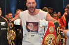 Britain's new world champion Tyson Fury, celebrates with the WBA, IBF, WBO and IBO belts. Photo / AP.