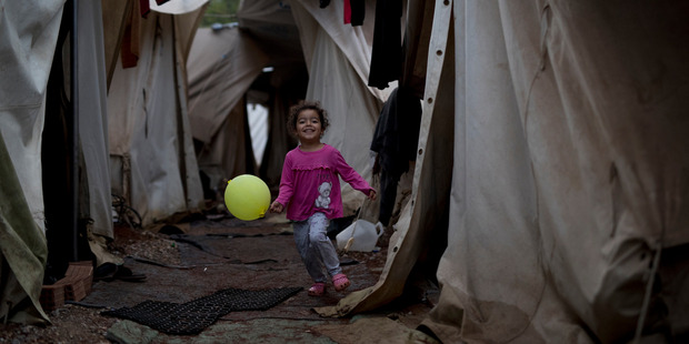 A Syrian girl holding a balloon runs through a light drizzle among tents at the Ritsona camp for refugees and other migrants north of Athens. Photo / AP