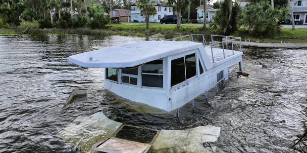 A boat sunk by high winds from Hurricane Matthew, sits on the shore of the Halifax River in Ormond Beach, Fla. Photo / AP