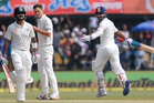 Indian batsman Ajinkya Rahane, right, celebrates his century as his team captain Virat Kohli, left, and New Zealand's bowler Trent Boult centre, look on during the second day. Photo / AP.