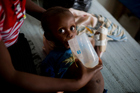 Cenelson Lundi, 13 months, a victim of cholera receives treatment as he gets help by her mother Etienne Chimene at the state hospital after Hurricane Matthew, in Jeremie, Haiti. Photo / AP