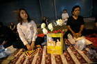 Thais wait outside Siriraj Hospital for the body of King Bhumibol Adulyadej to be carried to Grand Palace in Bangkok. Photo / AP