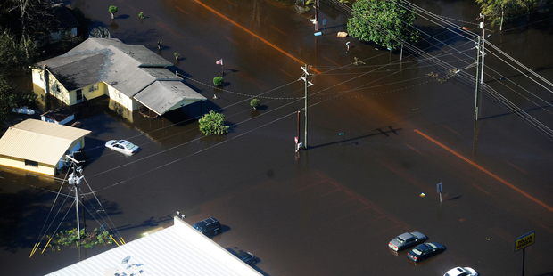 Floodwaters surround homes, businesses and cars in Nichols, South Carolina. Photo / AP