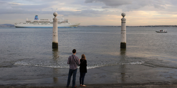 A young couple watch the cruise Thomson Celebration sail past. Photo / AP