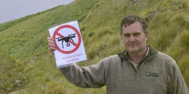 Department of Conservation ranger Lyndon Perriman holds a no-fly zone sign that has been installed after a drone crashed near an albatross nesting site. Photo: Gerard O'Brien/ODT