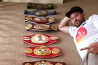 Tyson Fury poses with his belts at his home but he is set to relinquish his titles. Photo / Twitter