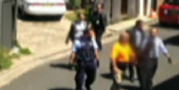 The teen is led away by police to be taken to Bankstown Police Station. Photo / 7 News