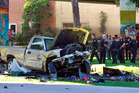 Police stand near the pickup truck that landed at Chicano Park after it flew off a ramp to the San Diego Coronado Bridge. Photo / AP