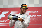 Lewis Hamilton celebrates on the podium after finishing third in Japan. Photo / Getty Images