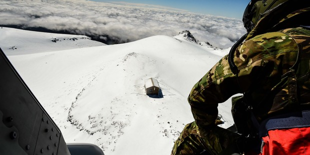 The NH90 chopper approaches Syme Hut, which sits a perch Mt Taranaki, 2000m above the ground. Photo / Supplied
