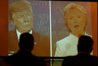 Viewers look on at the big screen television showing the third and final presidential debate between Democrat Hillary Clinton and Republican Donald Trump. Photo / AP