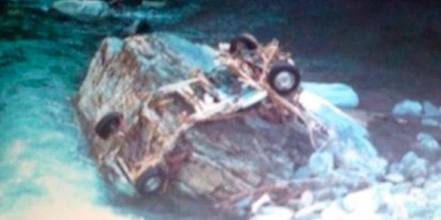 Photo shows the wrecked chassis of the rental vehicle hired by Canadians Connor Hayes and Joanna Lam, wrapped around a boulder in the Haast River. Photo / NZ Police