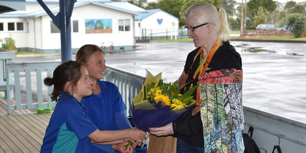 Paralympic hero Emma Foy is presented with flowers by Danielle Lowe (centre) and Payton Hutchinson at Dargaville Primary School.