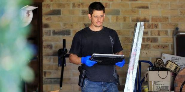 Police take away a laptop from the family home. Photo / Craig Greenhill, News Corp Australia