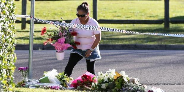 A woman places flowers outside the family murder crime scene in Davidson. Photo / Craig Greenhill, News Corp Australia
