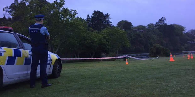 Police this morning guard the scene where a woman's body was found in the Waikato River on Ann St, Hamilton, last night. Photo / Belinda Feek