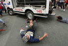 Protesters lie on the ground after being hit by a police van during a rally in front of the U.S. embassy in Manila. Photo / Rob Reyes-AFP-Getty Images via Washington Post
