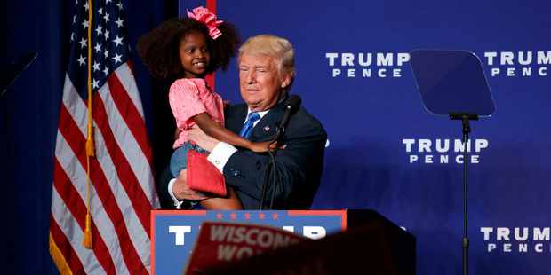 Republican presidential nominee Donald Trump suffered an 'awkward' moment while holding a child during a rally. Photo / AP