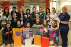 Rototuna Junior High students present their knitted items to NICU charge nurse manager Christine Woolerton (far right).